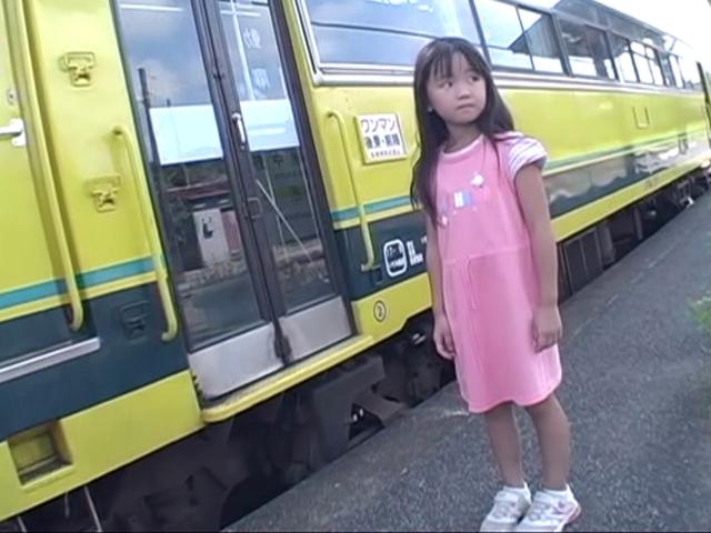 電車の隣に立つピンクのワンピース姿のU12JSジュニアアイドルえりかちゃん