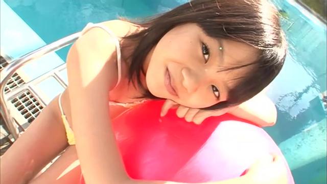U12ジュニアアイドル宮田飛鳥ちゃんが黄色のビキ二姿でプールサイドでバランスボールに身体を預けてカメラ目線でポージングしている