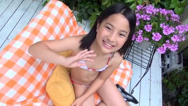 ソファーの上に座って手を振る白のビキ二姿のU12JSジュニアアイドル中村早希ちゃん
