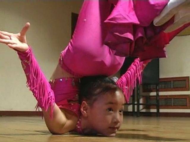 ピンクの舞台衣装で雑技を披露するU12ジュニアアイドル明々ちゃん。顔で全身を支えている