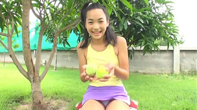 ミニスカテニスウェア姿で座ってテニスボールを手に微笑むU12JSジュニアアイドル清水美蘭ちゃん。スカートの中の白のビキ二が見えている