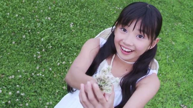 白のワンピース姿のU12JSジュニアアイドル黒宮れいちゃんが摘んだお花をこちらに差し出している
