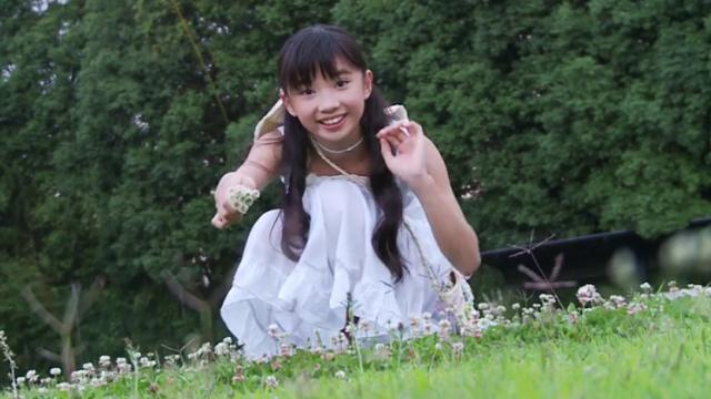 摘んだお花を手に座りながらこちらに笑顔を向ける白のワンピース姿のU12JSジュニアアイドル黒宮れいちゃん
