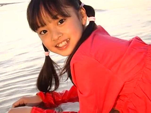 ビーチで寝そべってポージングする赤のワンピース姿のU12JSジュニアアイドル河西莉子ちゃん